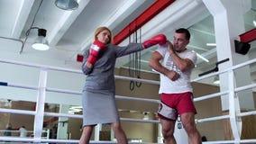 Милая женщина в перчатках платья и бокса тренируя с тренером на боксерском ринге видеоматериал