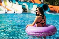 Милая женщина в розовом резиновом кольце в скольжении бассейна близко стоковая фотография rf