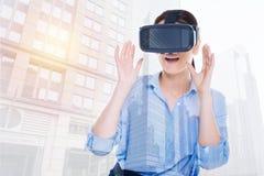 Милая женщина в руках повышения шлемофона VR в сюрпризе Стоковое Фото