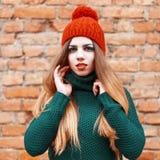 Милая женщина в стильные одежды стоит около кирпичной стены Стоковые Фотографии RF