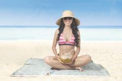 Милая женщина держит кокос на пляже Стоковое Изображение RF