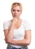 Милая женщина думая с ее рукой на подбородке Стоковые Изображения