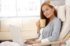 Милая женщина используя компьтер-книжку имея чай Стоковые Фото