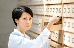 Милая женщина ищет что-то в картотеке Стоковые Фотографии RF