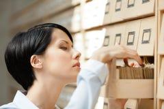 Милая женщина ищет что-то в картотеке Стоковое фото RF