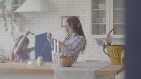Милая женщина и небольшая девушка кладя на голубые рисбермы в кухню Подготовка на праздник пасхи Бутылки акрила видеоматериал