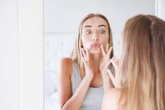 Милая женщина касаясь ее губам пока смотрящ в концепции заботы зеркала, красоты и кожи, морщинках стоковые фотографии rf