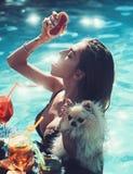 Милая женщина наслаждаясь свежими соком и коктейлем в бассейне стоковые изображения rf