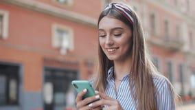 Милая женщина нося в голубом и белом striped платье используя приложение на положении смартфона на старой улице города r акции видеоматериалы
