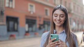 Милая женщина нося в голубом и белом striped платье используя приложение на смартфоне идя на старую улицу города r акции видеоматериалы