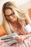 Милая женщина ослабляя на газете Рединга кровати стоковая фотография rf