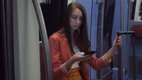 Милая женщина отправляя SMS на ее смартфоне пока принимающ поезд в аэропорт видеоматериал