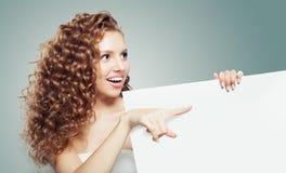 Милая женщина показывая белую пустую предпосылку бумажной доски с космосом экземпляра для рекламировать маркетинг или размещение  стоковая фотография rf