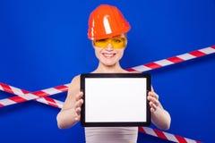 Милая женщина построителя в белой рубашке, поясе построителя, шлеме, строении Стоковое Фото