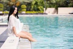 Милая женщина сидя бассейном Стоковые Изображения