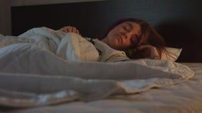 Милая женщина спит в спальне со светом на после этого внезапно будит и усмехается сток-видео