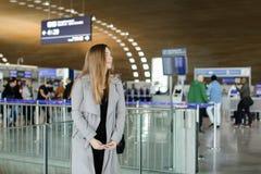 Милая женщина стоя на авиапорте, нося пальто Стоковая Фотография RF