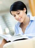 Милая женщина дела отдыхает на софе с книгой Стоковые Фотографии RF