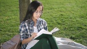 Милая жизнерадостная девушка читает в парке видеоматериал