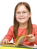 Милая жизнерадостная книга чтения маленькой девочки стоковая фотография rf