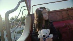 Милая жизнерадостная маленькая девочка с плюшевым медвежонком едет на carousel акции видеоматериалы