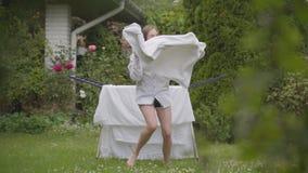 Милая жизнерадостная молодая женщина имеет потеху поя и танцуя на задворк пока делающ работу дома с бельем washday сток-видео