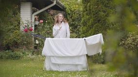 Милая жизнерадостная молодая женщина имеет потеху поя и танцуя на задворк пока делающ работу дома с бельем washday видеоматериал