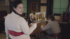 Милая жирная девушка с 3 стеклами пива на подносе в ресторане пива Официантка приносит пиво до 2 парня к сток-видео