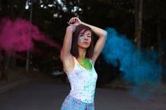 Милая загоренная женщина при короткие волосы представляя с взрывать Holi стоковые изображения