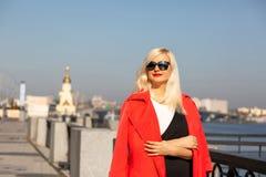 Милая зрелая женщина в солнечных очках, представляя на городе весной скопируйте космос стоковое изображение