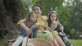 Милая зрелая женщина сидя под деревьями в парке с 2 милыми внучками Девушки есть яблоки смотря прочь сток-видео