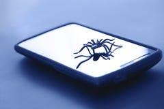 Милая игрушка паука представляя на поверхности дисплея устройства Стоковое Фото