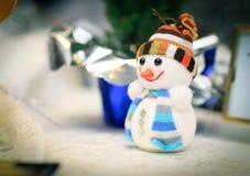 Милая игрушка снеговика и поздравительная открытка на таблице рождества Стоковая Фотография