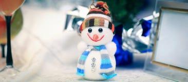 Милая игрушка снеговика и поздравительная открытка на таблице рождества Стоковая Фотография RF