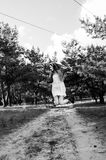 Милая и довольно молодая белокурая девушка в белом платье, куртке джинсов и черных ботинках скача на дорогу песка стоковая фотография