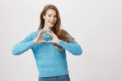 Милая и нежная женщина с светлыми волосами, нося модным свитером и показывать знак сердца около комода пока усмехающся Стоковая Фотография