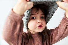 Милая кавказская маленькая девочка играя peekaboo со шляпой зимы теплой серой, нося свитер изолированный на белой предпосылке сту стоковые изображения rf