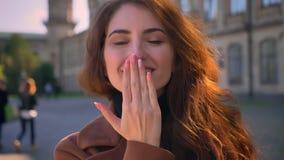 Милая кавказская модель брюнета стоит outdoors в sunshines и крупный план отправляет дуя поцелуй на камере, холодок акции видеоматериалы