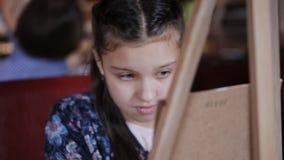 Милая картина маленькой девочки с акриловыми цветами на холсте, в ярко освещенной комнате сток-видео