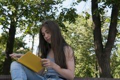 Милая книга чтения девочка-подростка сидя на стенде в парке, изучать внешний Стоковое Фото