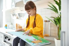 Милая книга чтения маленькой девочки в кухне стоковая фотография rf
