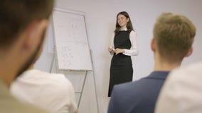 Милая коммерсантка представляя новый проект к партнерам с диаграммой сальто Руководитель группы давая представление коллегам внут видеоматериал