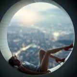Милая красивого молодого взрослого тонкая и привлекательная женщина чувственности в платье элегантности модном лежа в круглом окн стоковые изображения