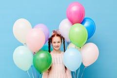 Милая красная с волосами девушка держа воздушные шары стоковая фотография