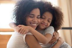 Милая ласковая африканская дочь матери и маленького ребенка обнимает объятие стоковое изображение