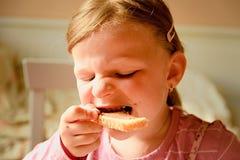 Милая малая девушка Малая девушка ест здравицу с сливк шоколада Малая девушка сидит в кухне Стоковое Фото