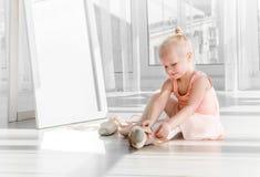Милая маленькая белокурая девушка сидя на поле и связывая ботинки балета Стоковые Фотографии RF