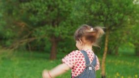 Милая маленькая девочка бежать в парке на солнечный летний день акции видеоматериалы