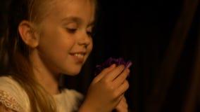 Милая маленькая девочка вдыхая сладостный нюх красивого цветка, наслаждаясь ездой качания сток-видео