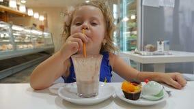 Милая маленькая девочка выпивает капучино видеоматериал